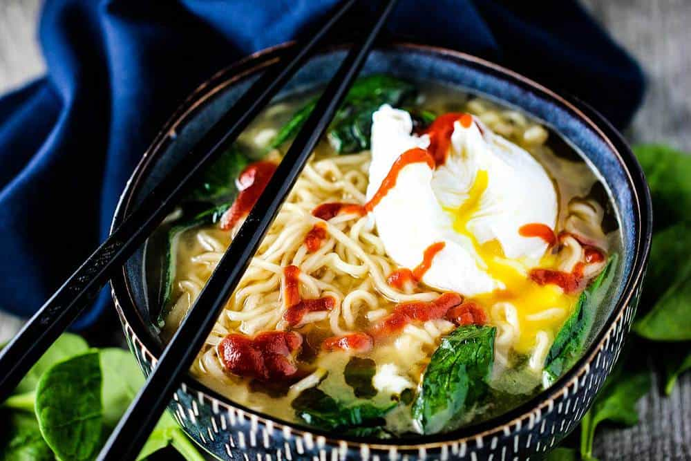 Spinach ramen noodle soup with poached egg in a blue bowl with chop sticks