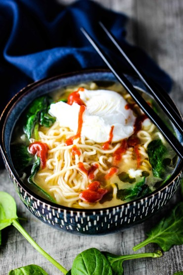 Spinach Ramen Soup with Poached Egg in a bowl with chop sticks on top