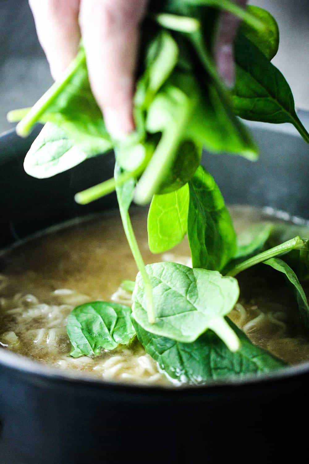 Baby spinach dropping into a pot of spinach ramen noodle soup