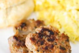 A close-up view of two maple sausage patties on a white plate with scrambled eggs and a biscuit.
