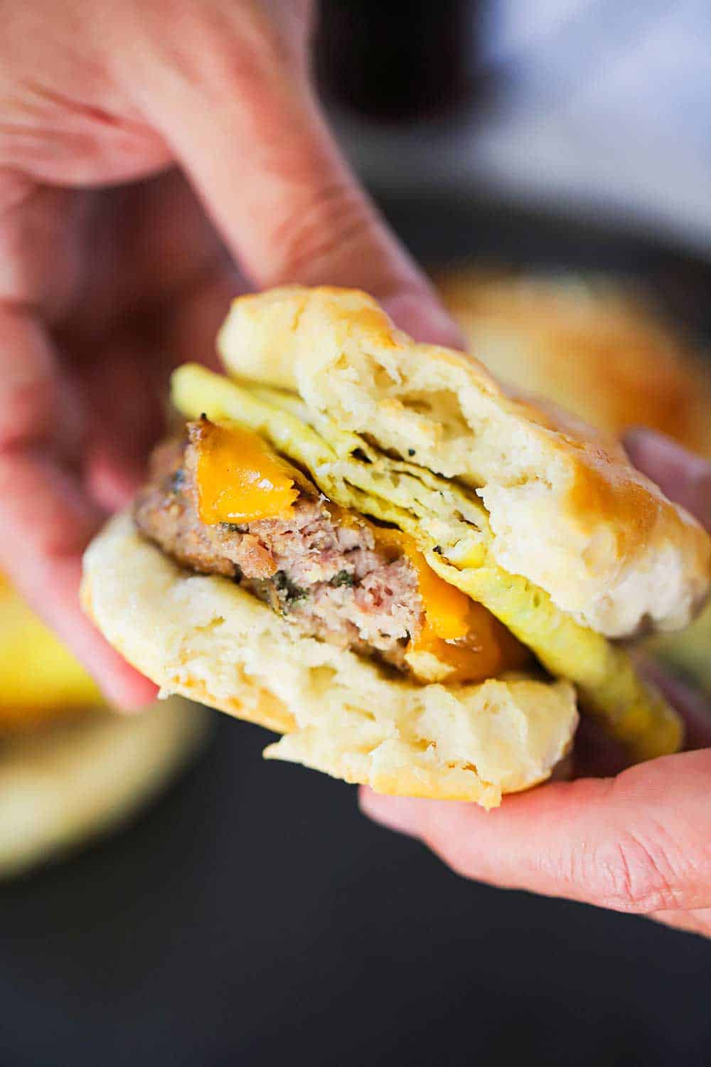 Two hands holding a sausage, egg, and cheese breakfast sandwich with a bite taken out it.