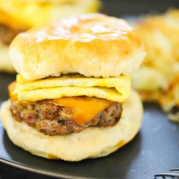 A sausage, egg, and cheese breakfast sandwich on a dark plate in front of hashbrowns.