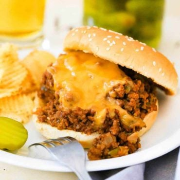 A sloppy joes sandwich on a white plate next to a jar of sliced pickles.