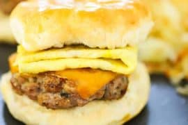A sausage, egg, and cheese biscuit sandwich on a circular dark grey plate with hashbrowns in the background.