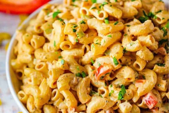 A large white bowl of freshly prepared Cajun Pasta Salad.