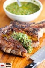 This is a grilled cowboy ribeye steak with chimichurri sauce on it