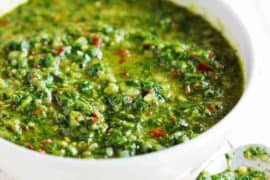 A white bowl of freshly made chimichurri sauce next to a spoon.