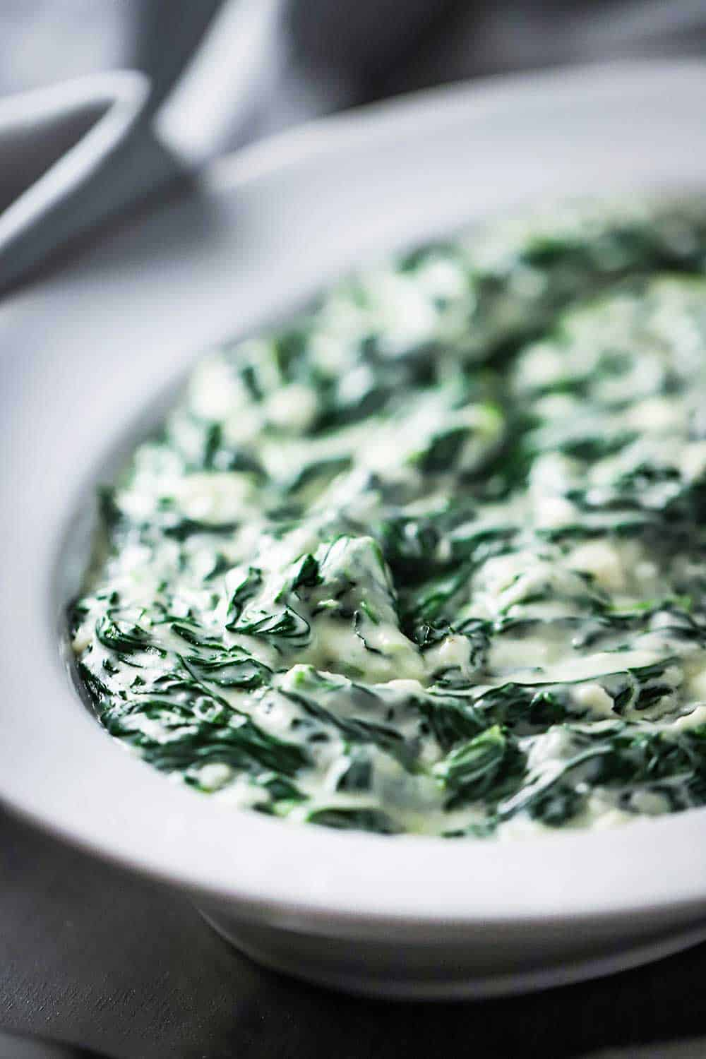 A white oval serving bowl filled with creamed spinach.