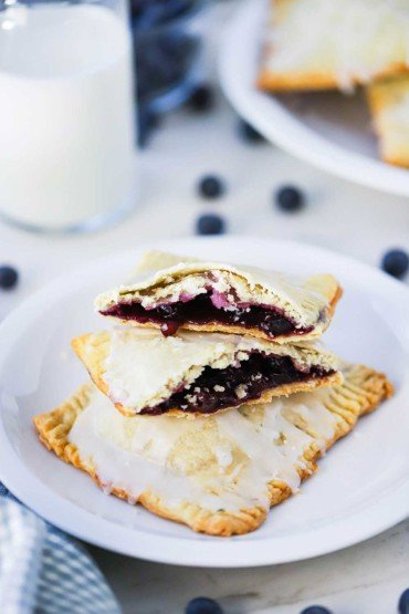A small white plate holding 2 homemade blueberry pop tarts, one that is split open on top, sitting next to a glass of milk.