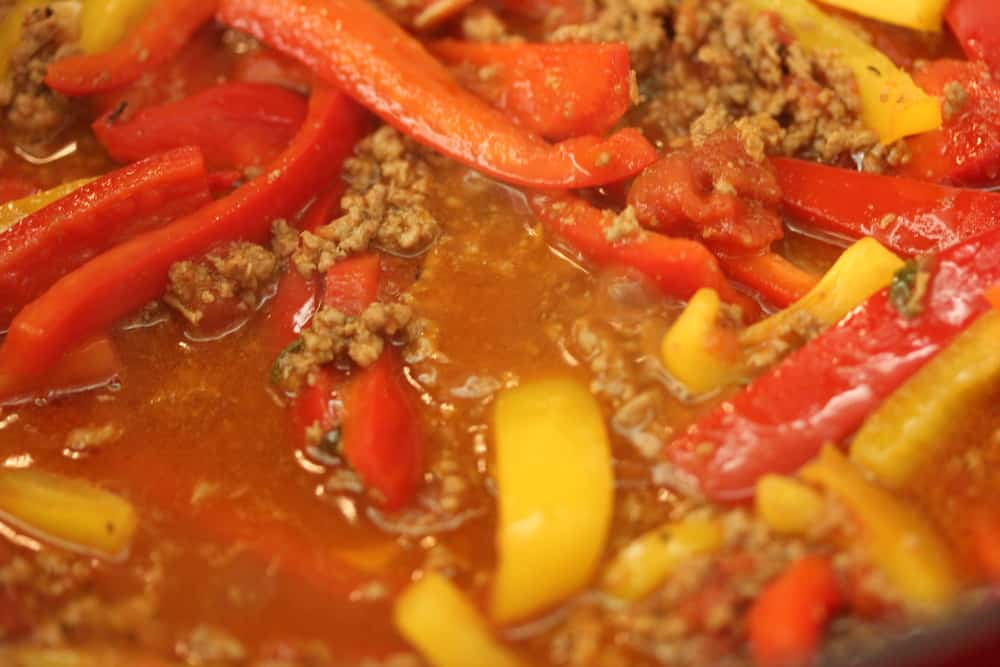 Lamb and pepper ragu simmering in a skillet.