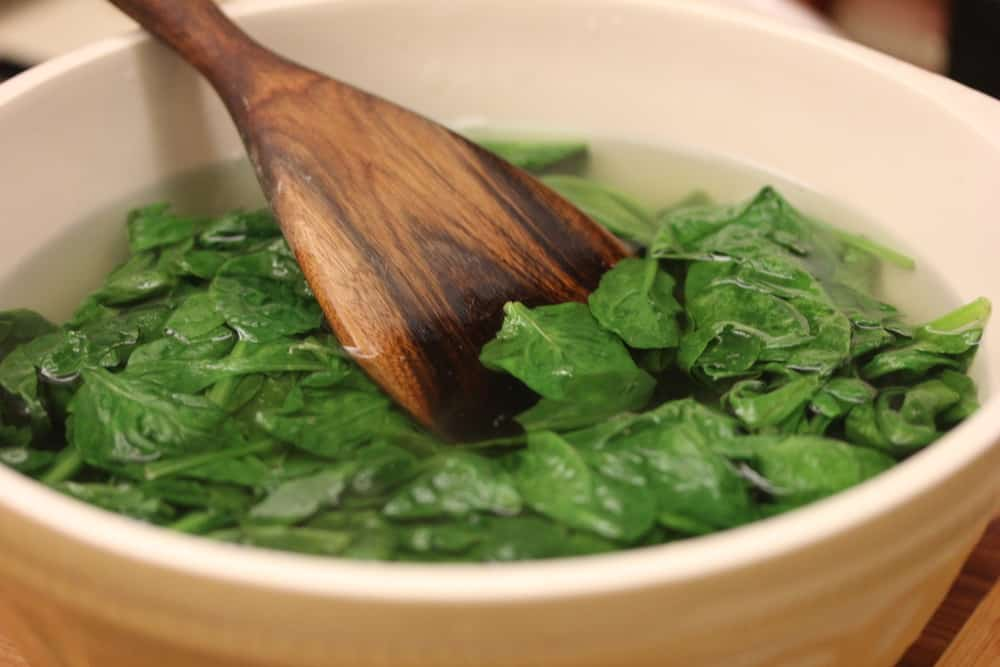 Blanched spinach cooling in a large bowl filed with ice water.