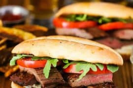 A Marinated Grilled Steak Sandwich on a wood cutting board