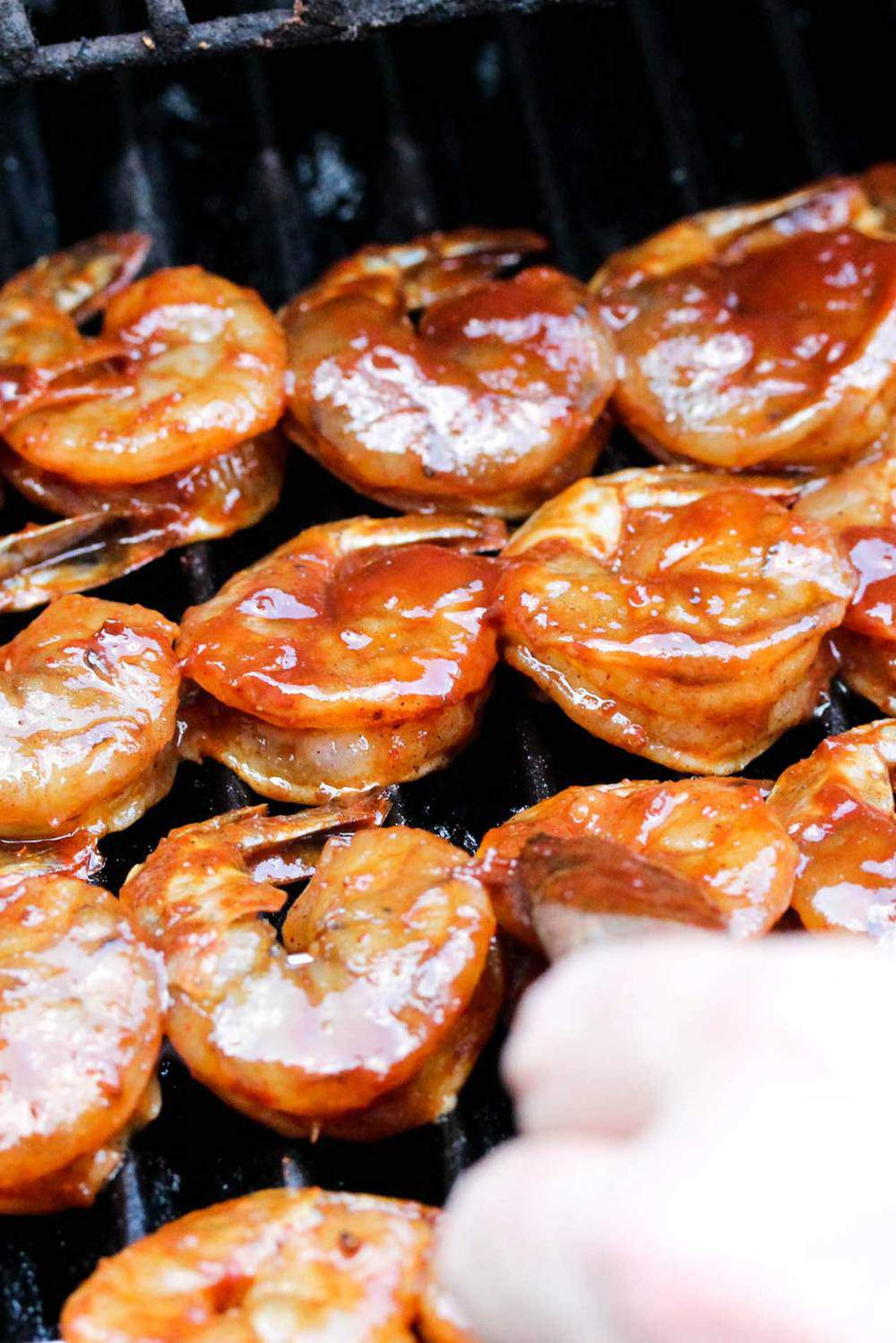 Shrimp on skewers on a grill with homemade BBQ sauce being brushed on.