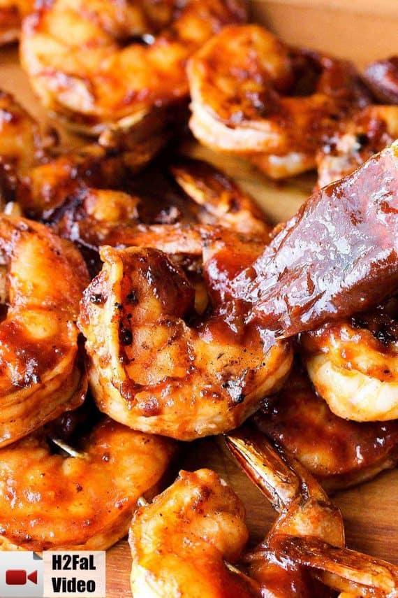 Grilled shrimp being brushed with homemade BBQ sauce