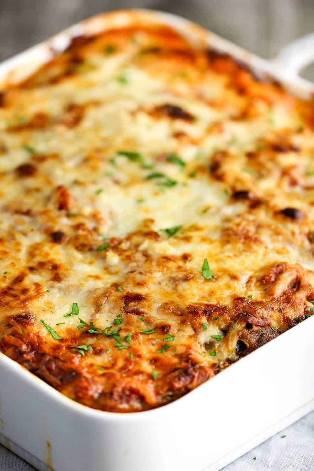 Authentic Eggplant Parmesan in a baking white dish.