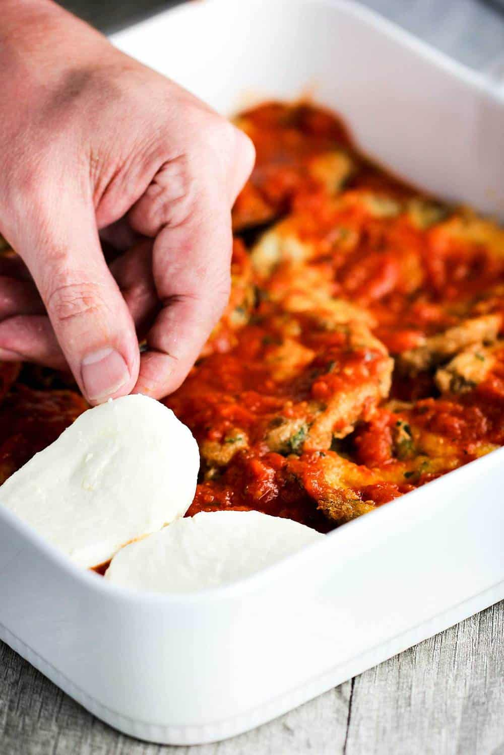 A baking dish of eggplant parmesan with layers of fresh mozzarella being layered in.