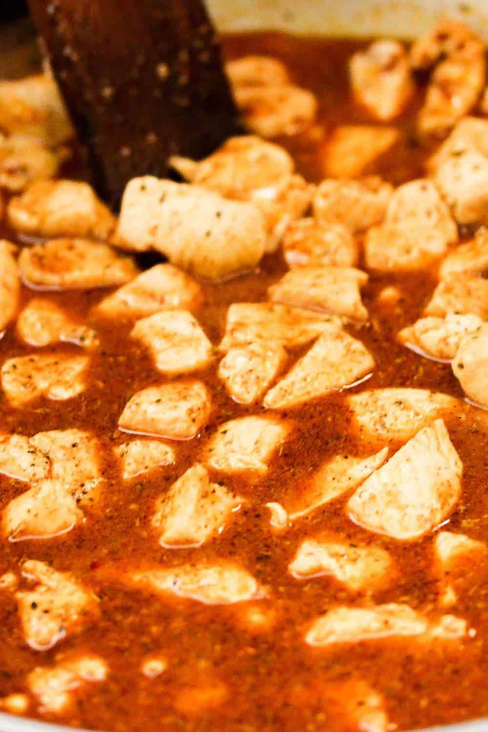 chicken pieces simmering in a Mexican sauce for chicken quesadillas
