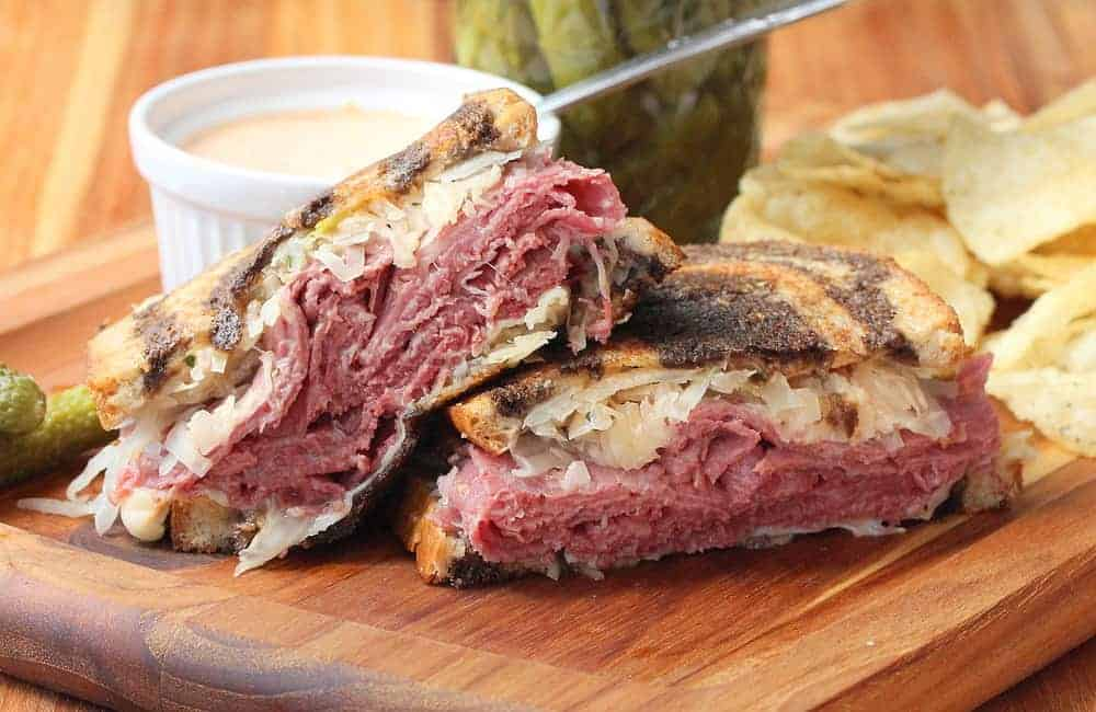 A Classic Reuben Sandwich sliced in half on a cutting board next to a dish of Russian dressing.