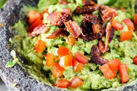 A molcajete filled with fresh guacamole topped with tomatoes and bacon