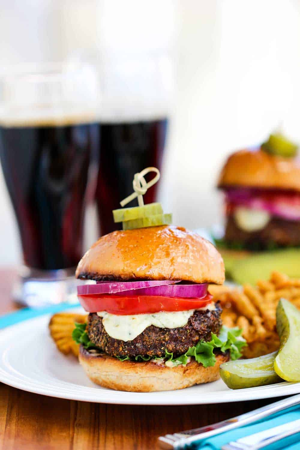 A black and bleu burger on a plate in front of two glasses of dark beer.