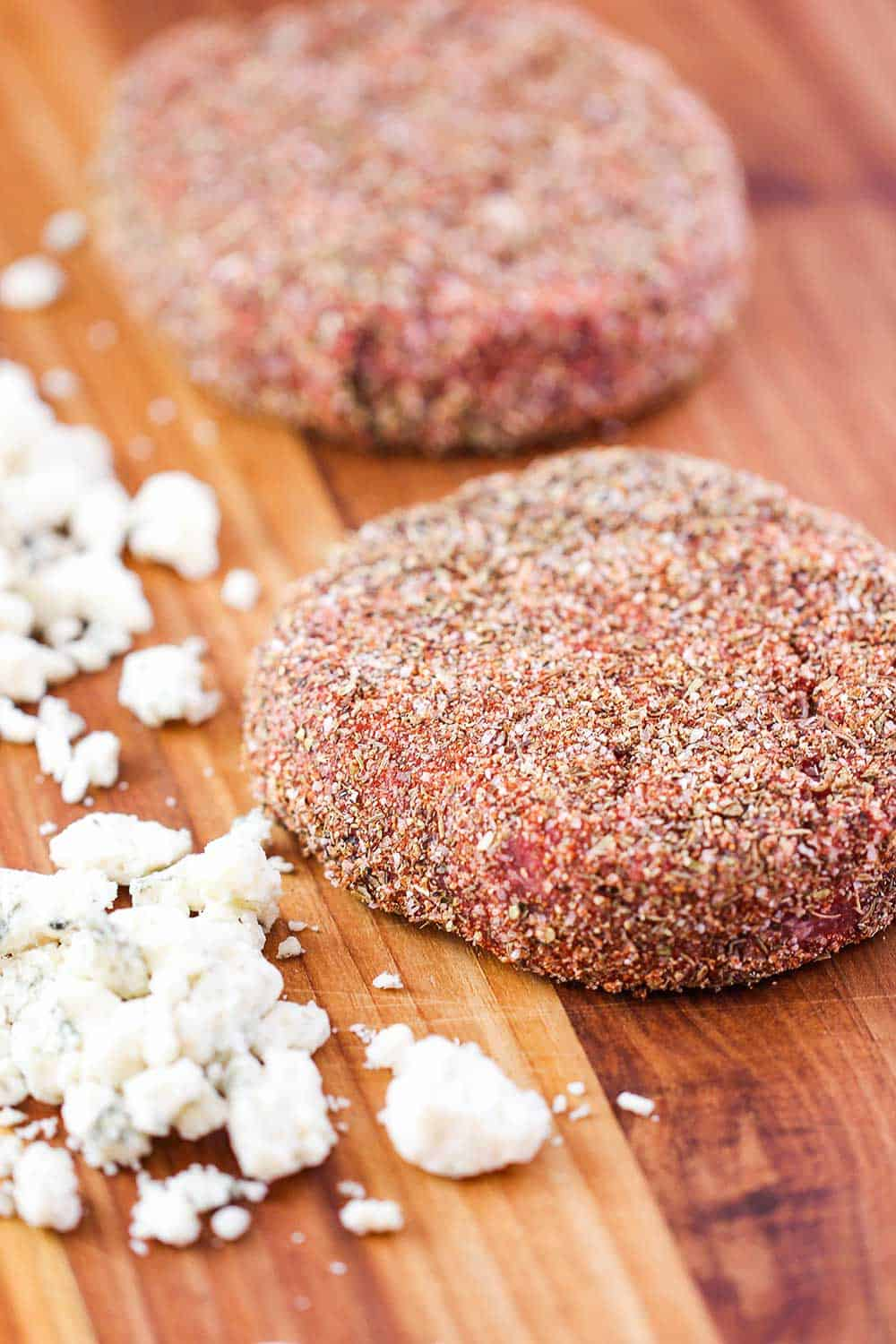 Uncooked sirloin burgers with blackening seasoning on them.
