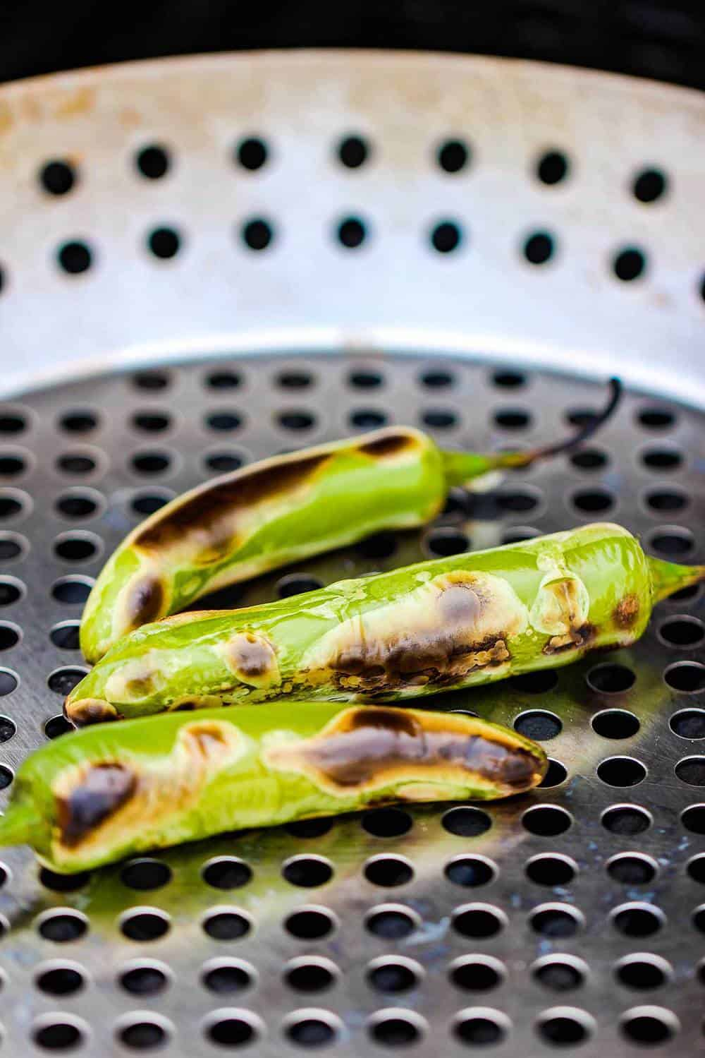 3 serrano peppers on a grill pan being roasted