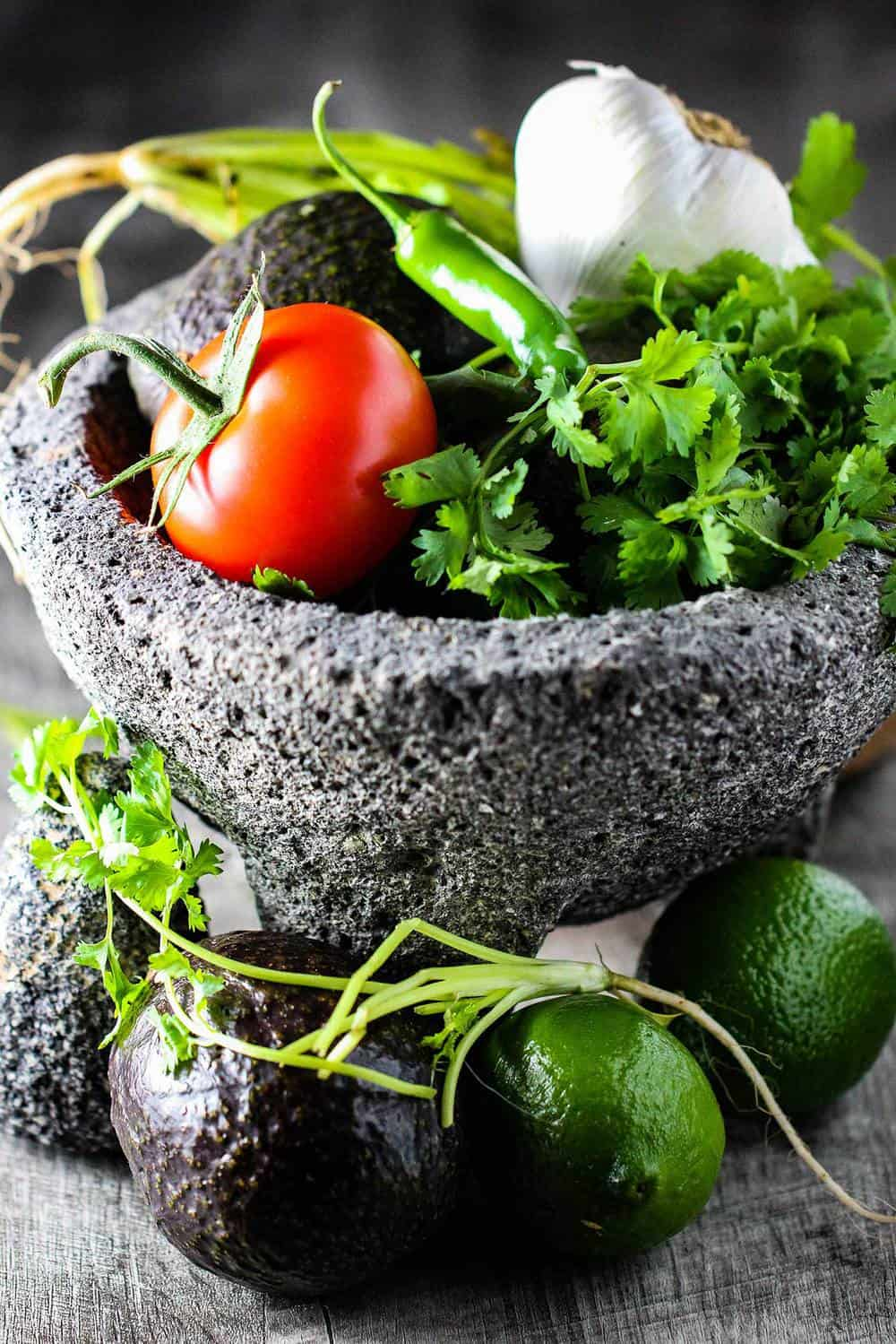 A molcajete filled with ingredients for making fresh guacamole