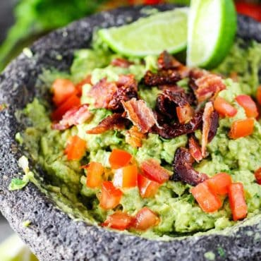 A molcajete filled with homemade fresh guacamole