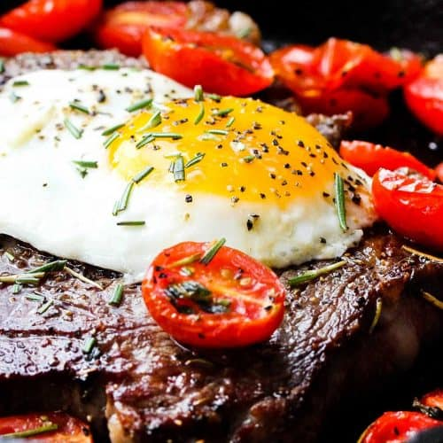 Ribeye steak and eggs with blistered cherry tomatoes in a cast iron skillet