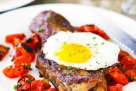 A view looking down on a white plate filled with a seared New York strip steak topped with a fried egg next to roasted tomatoes with a glass of orange juice nearby.