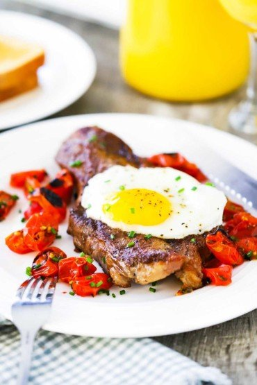 steak and eggs with roasted cherry tomatoes in a cast iron skillet