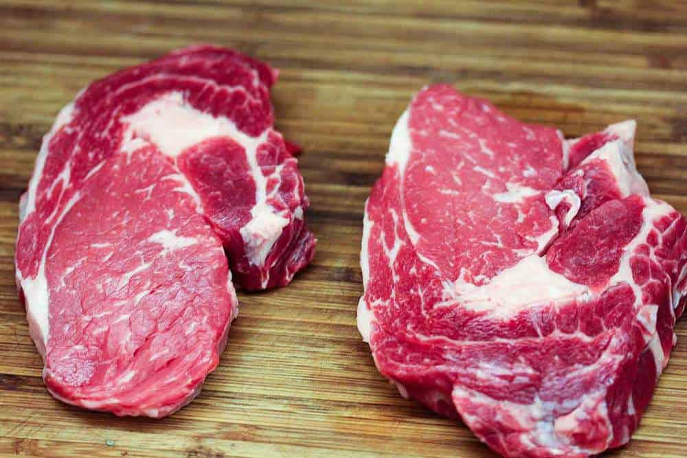 uncooked ribeye steaks on a cutting board