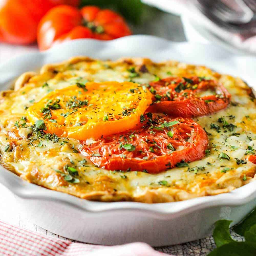 Southern Tomato Pie in a white pie dish with tomatoes nearby.
