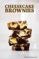 A stack of four square chocolate and cheesecake brownies on a white surface.