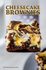 A chocolate and cheese cake brownies being held up on a metal spatula.