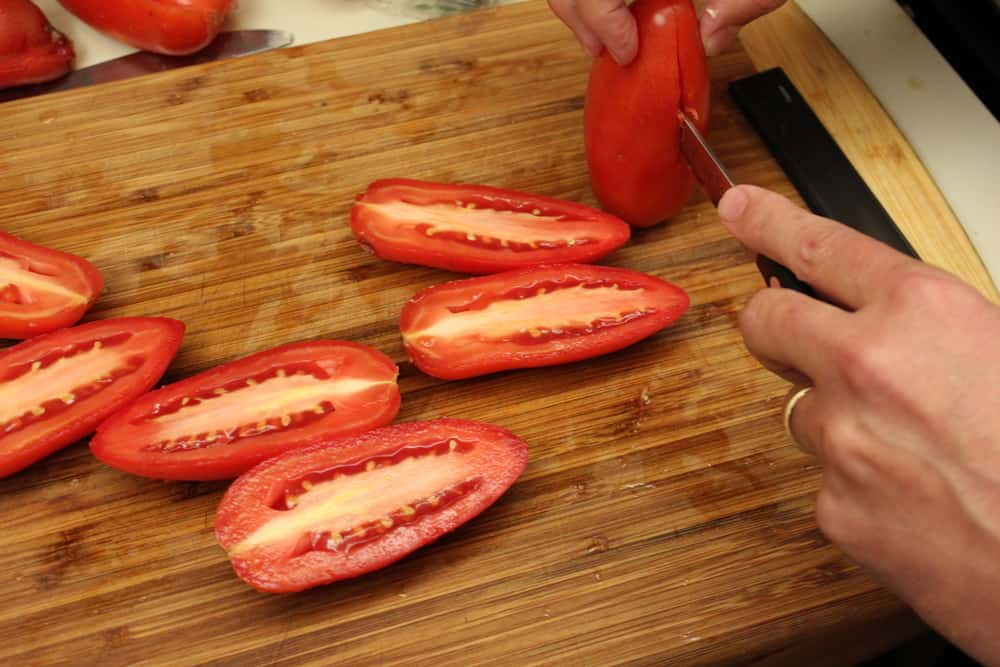 Slice the Roma tomatoes lengthwise, down the center