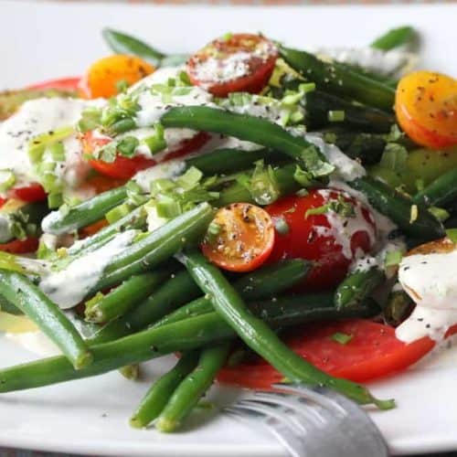 Green bean and tomato salad on a white plate with a fork next to it.