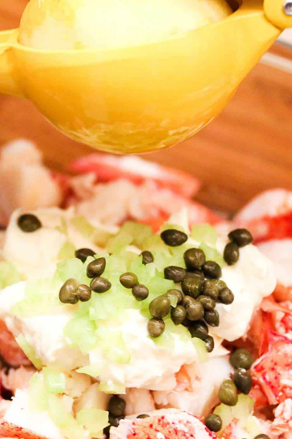 A bowl of lobster roll ingredients of lobster meat, capers and fresh lemon juice.