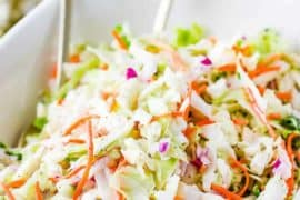 A large white bowl containing freshly made homemade coleslaw.