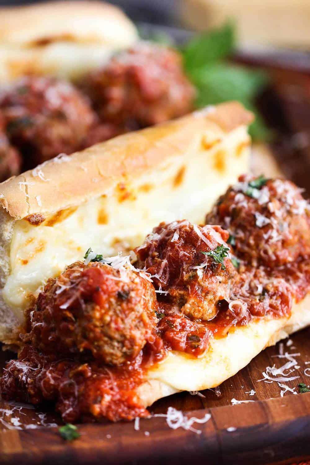 Homemade Italian Meatballs in side a cheesy meatball hero sandwich on a cutting board.