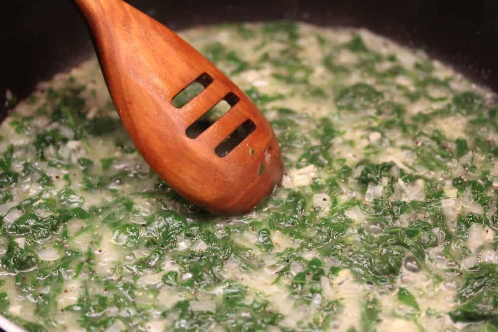 A large skillet filled with chopped spinach, garlic, onions, and butter being sautéed with a wooden spoon in the skillet