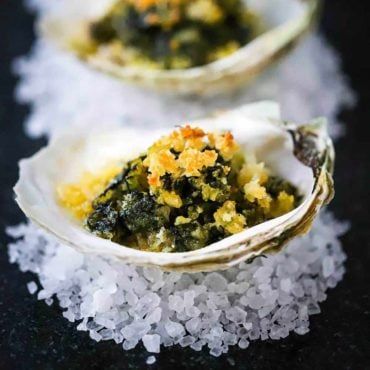 A dark grey trey filled with oysters Rockefeller sitting on small piles of rock salt.