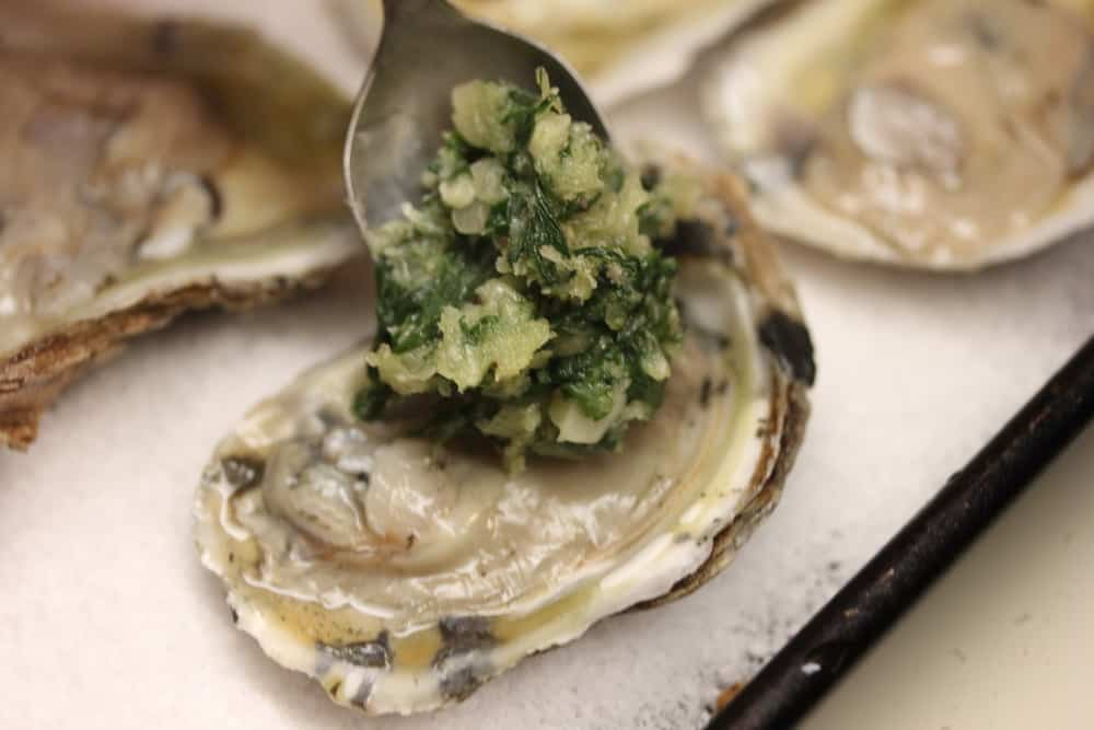 A spoon adding a small mound of spinach topping on an oyster for oysters Rockefeller.