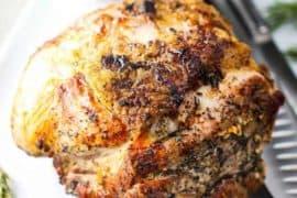 Slow Roasted Pork Shoulder on a platter with a side of gravy