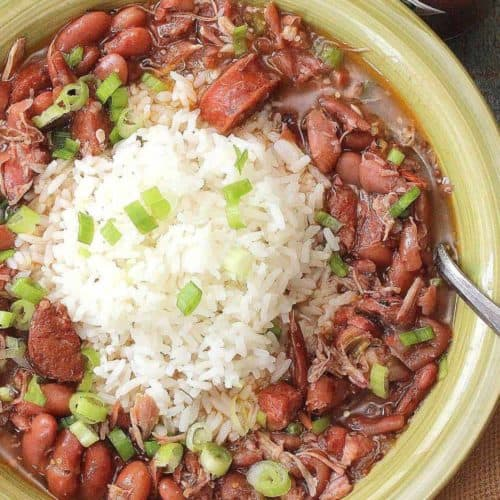 A green bowl holding red beans and rice with white rice in the center.