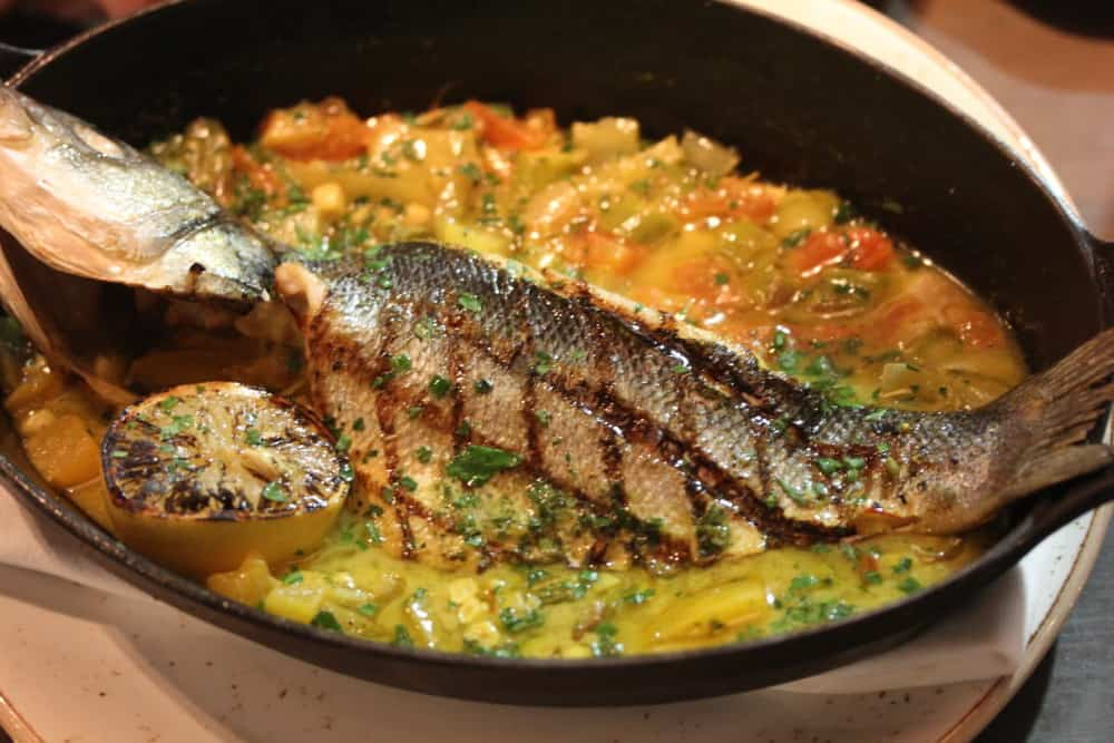 Roasted whole bronzino with Jersey corn, heirloom cherry tomatoes, roasted fennel and asparagus in a saffron herb broth