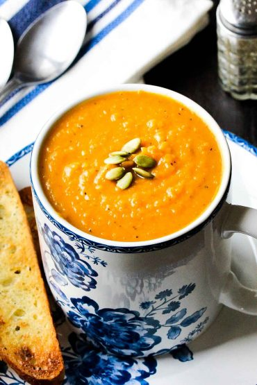 roasted butternut squash soup in a large cup with toast next to it