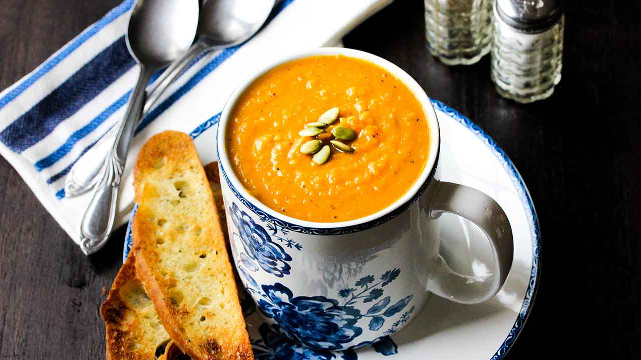 roasted butternut squash soup in a cup on a plate