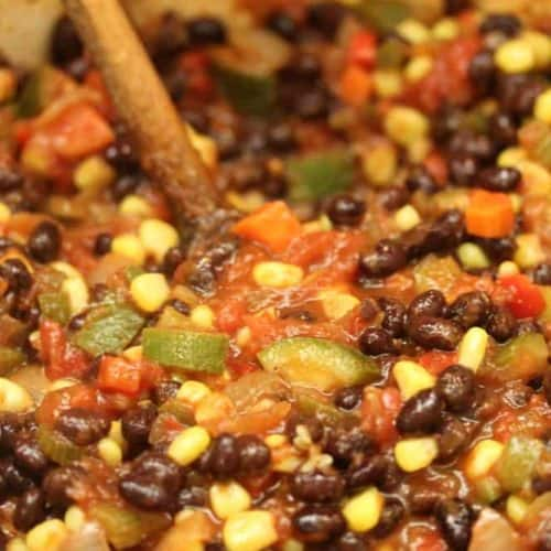 A wooden spoon stuck into a large pot of vegetarian black bean chili