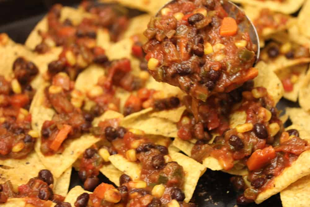 A spoon lowering a mound of vegetarian chili onto a baking sheet filled with chips, tomatoes, chili for vegetarian black bean nachos.